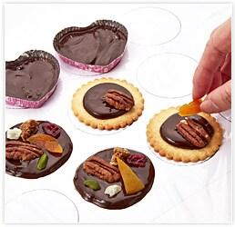 チョコが冷えて固まらないうちに、手早くナッツやドライフルーツを盛り付けて出来上がりです。大きな具材から盛り付けていくとバランスよく仕上がりますよ♪