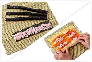 バラの巻き寿司の準備をします。巻き簾にラップを広げ、海苔より3cm短いサイズに薄焼き卵を広げ、スモークサーモン、イクラ、ピンクの寿司飯をパラパラと置き、巻き込むようにぐるぐると巻いて、ラップで丸めたまま止めておきます。 花の巻き寿司の準備をします。海苔を1/4に切ったものを5枚用意し、ピンクの寿司飯を薄く伸ばして巻いたものを5本用意します。