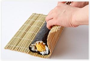 巻き寿司を仕上げます。海苔の表(つるつるしたほう)を下にし、上2cm、下5mmぐらい海苔の部分を残して寿司飯を薄く広げます。そこに、太い卵焼きを巻くと「にこちゃん」。バラのお花を巻くと「バラの巻き寿司」、ピンクの細巻5本と細い卵焼きを巻くと「お花」の飾り巻き寿司のできあがりです。切って、ニコちゃんに顔をつけて盛り付けてくださいね。
