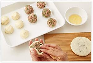 生地と餡をそれぞれ10等分して丸める。手にこめ油を付け、生地を手のひらで丸く広げて、餡を包む。肉汁が漏れないようにしっかりと閉じ、油をひいたまな板の上で直径10cmぐらいに押し広げる。
