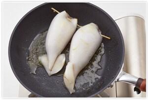 フライパンに、オリーブオイル、まな板でつぶしたにんにく、鷹の爪を入れて火にかけ、弱火でゆっくりと加熱し、にんにくの香りが出たら、にんにくは取り出して捨てる。中火にし、3のイカの両面を焼く。