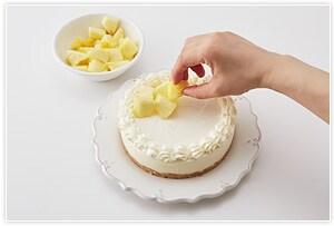仕上げ。周囲に砂糖を入れて泡立てた生クリームを絞り、好みにパイナップルをカットし、ケーキに盛り付ける。あればミントの葉を散らすとより爽やかな見た目に仕上がります。