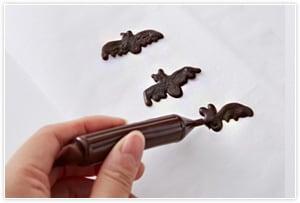 チョコペンでコウモリを作る、少し厚みを出してコウモリの形に絞り出して、しっかり冷やす。はがして裏のツルッとした方を表にして使う。その他お好みの飾りをつけて完成。