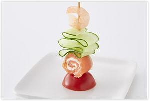 きゅうりはピーラーで薄切りに、エビはゆでておき、プチトマトは1/2に切る。えび→フリル状に折りたたんだきゅうり→サーモン→トマトの順に串に刺す。