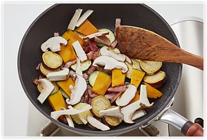 フライパンを中火にかけ、こめ油を入れてベーコンを炒めます。ベーコンに軽く火が通ったら、ズッキーニ、サツマイモとかぼちゃ、キノコの順に入れて炒めます。