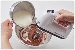 チョコの生クリームを作ります。ボールに刻んだチョコを入れ、電子レンジ500Wで1分程度温めて溶かします。生クリームに砂糖を加え、トロトロ程度の3分立てぐらいに泡立てます。チョコのボールに少しずつ生クリームを入れながら泡立てていくと完成。混ぜすぎると分離するので注意。