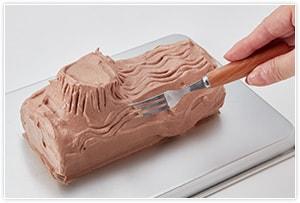 ケーキに【3】をたっぷりと塗り、フォークで木を模して線を描きます。茶こしにココアを入れて、ゆっくりと全体に振りかけたら、仕上げにお好みの飾りをつけて出来上がりです。少し冷蔵庫で冷やし固めてからいただく方がなじんで美味しいです。