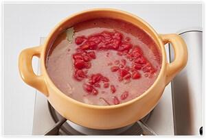 トマト缶と、トマト缶1杯分の水、コンソメとローリエを入れたところに残りの野菜を入れます。
