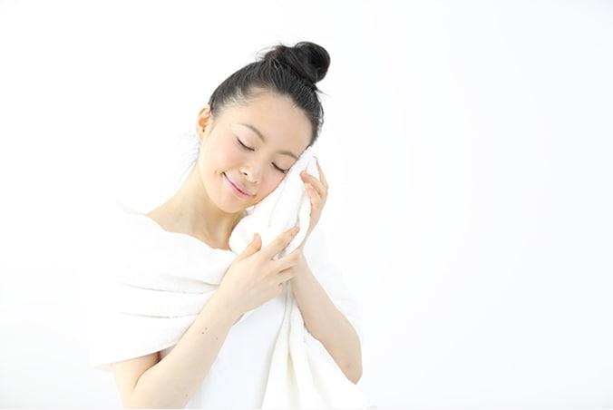 ホットタオルをでむくみを解消する女性 ホットタオルでまぶたを温めると血行がよくなりむくみが解消されます