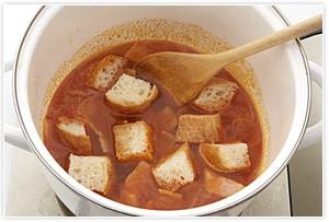 2に水、コンソメを入れてひと煮立ちさせたら、フランスパンを入れ、塩、ブラックペッパーで味をととのえる。