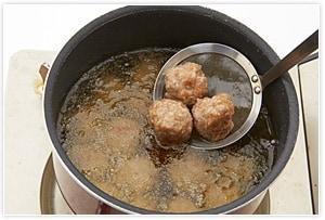 あげ油が冷たいところからさつまいもを入れて中火にかけ、じっくり中まで火を通す素揚げにします。次は中温のまま丸めた肉だんごを揚げ、ともに油を切っておきます。