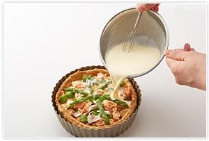 器にチーズ、タマネギ、アスパラ、マッシュルーム、鮭の順に敷き込み、これを2回繰り返します。アパレイユを流し込み、上に飾り用のアスパラを並べ、チーズをふりかけます。190℃に温めたオーブンで40分焼いてできあがりです。