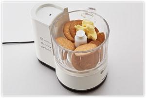 フードプロセッサーか、厚手のビニール袋の中にビスケットとバターを入れ、 砕いて混ぜる(細かくしすぎない)。それを、ケーキの型の底に敷き込む(あまり強く押し付けずふんわりと)。