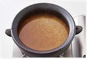 2米を洗ってざるで水をしっかりと切り、土鍋に入れます。❶のだし460mlと酒、しょうゆ、みりんを入れます。