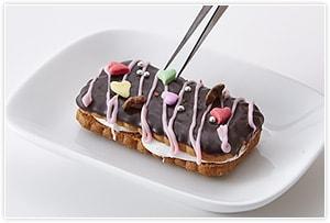 マシュマロをサンドするようにもう1枚のクッキーを乗せて少し押してサンドします。溶かしたチョコを塗り、好みの飾りつけをして完成です。チョコペンで文字などを描いてもかわいい。