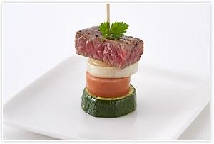 具材をフライパンでこんがり焼き、ズッキーニ→フランクフルト→たまねぎ→ステーキの順で刺し、パセリを飾る。