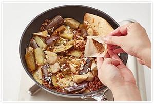 3にナスとサッと揚げたピーマン、ねぎのみじん切り、あらかじめ混ぜておいた(B)を入れぐつぐつ煮立てて水分が少なくなってきたら出来上がり。仕上げに山椒香味こめ油と花椒をふりかけ、パクチーを飾る。