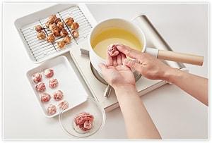 豚こま切れ肉に、塩と酒を振りかけてもみ、片栗粉をまぶし、小さめの肉団子状に丸め、150〜160℃の低温の油でじっくりキツネ色になるまで揚げます。