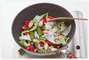 フライパンにこめ油を入れ、夏野菜を炒めます。