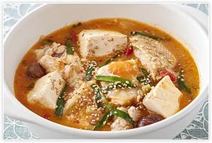 《豆腐キムチチゲ風》  上の材料でできた参鶏湯に、キムチ200g、豆腐1丁(1/8に切る)、ニラ1/6束(4cmに切る)を追加して鍋にうつして再沸騰させ、溶き卵2個を回し掛ければ、キムチチゲ風の辛味とボリュームのあるスープとなります。