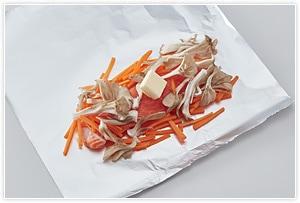 切ったアルミホイルにくっつき防止に適量の油を塗ってから鮭の皮目を下にして置きます。鮭一切れずつに舞茸とニンジンを鮭の上や横に添え、上からバターそれぞれ1かけずつをのせて包み、酒小さじ1ずつを入れて包みます。