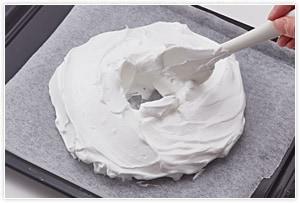 オーブンは140℃に予熱しておきます。オーブンペーパーの上にゴムベラでリース型に【2】を乗せます。(最初に高さのある丸を作り、後で中央に穴をあけるときれいにできます。)